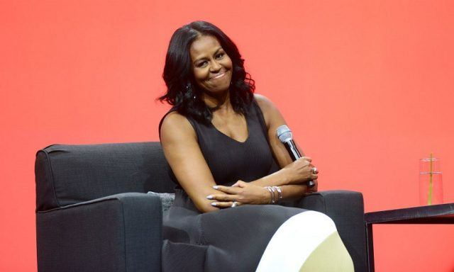 Michelle Obama sitting on a couch during a panel on stage.