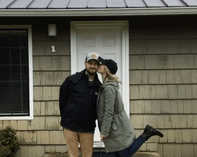 Tyson and Michelle Spiess posing for a cute photo in front of a home.
