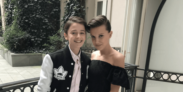 Millie Bobby Brown and Noah Schnapp posing together on a balcony.