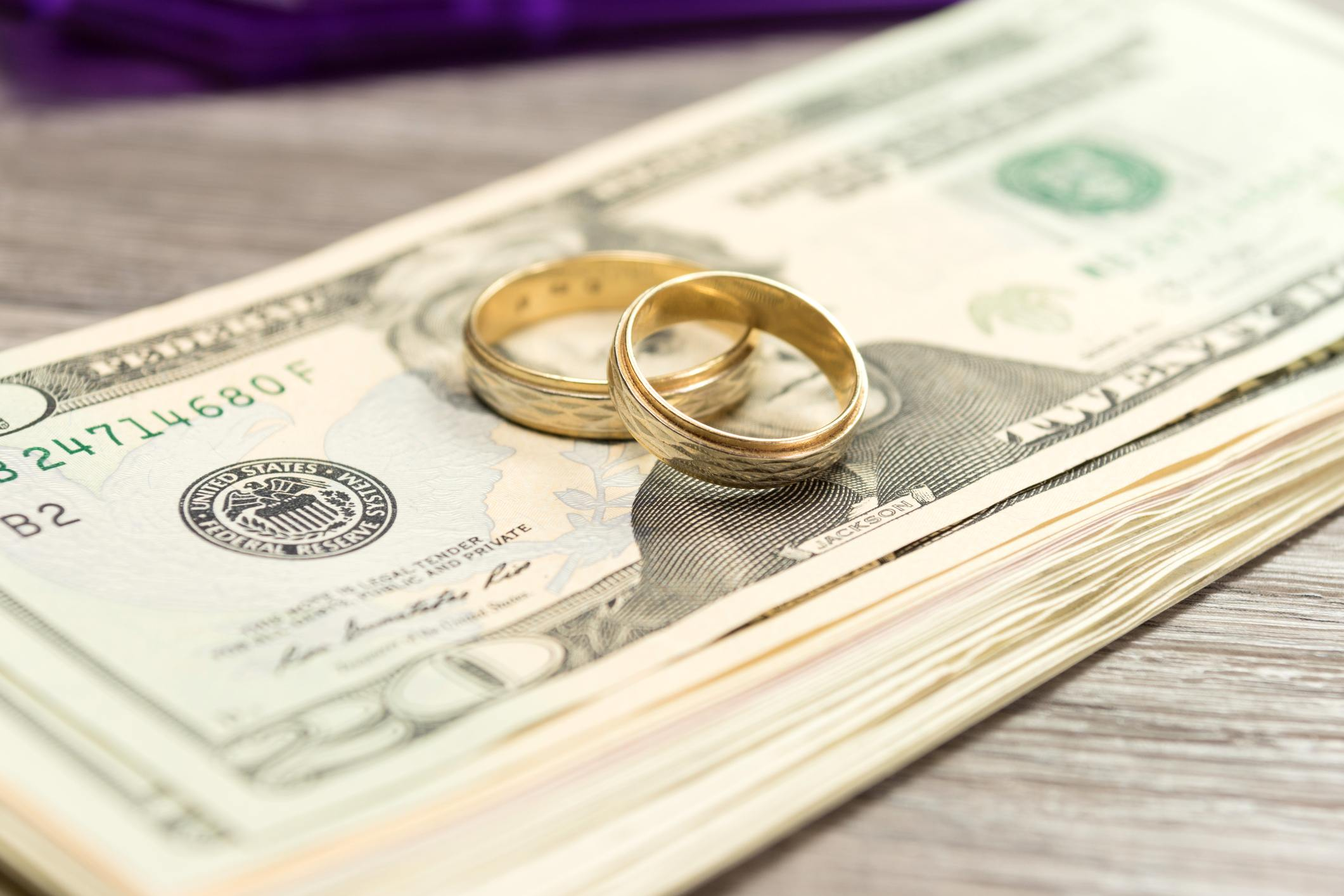 Wedding rings on top of stack of money.