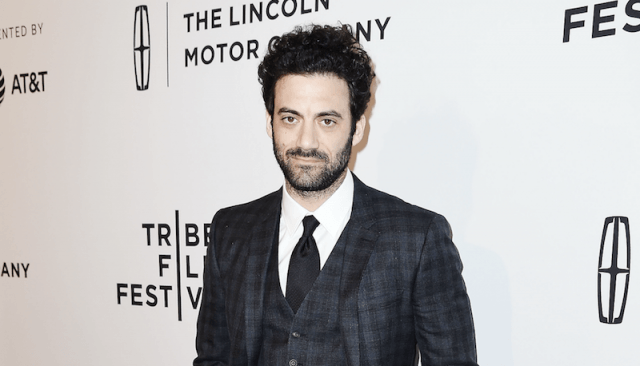 Morgan Spector smiling while wearing a black three-piece suit on a red carpet.