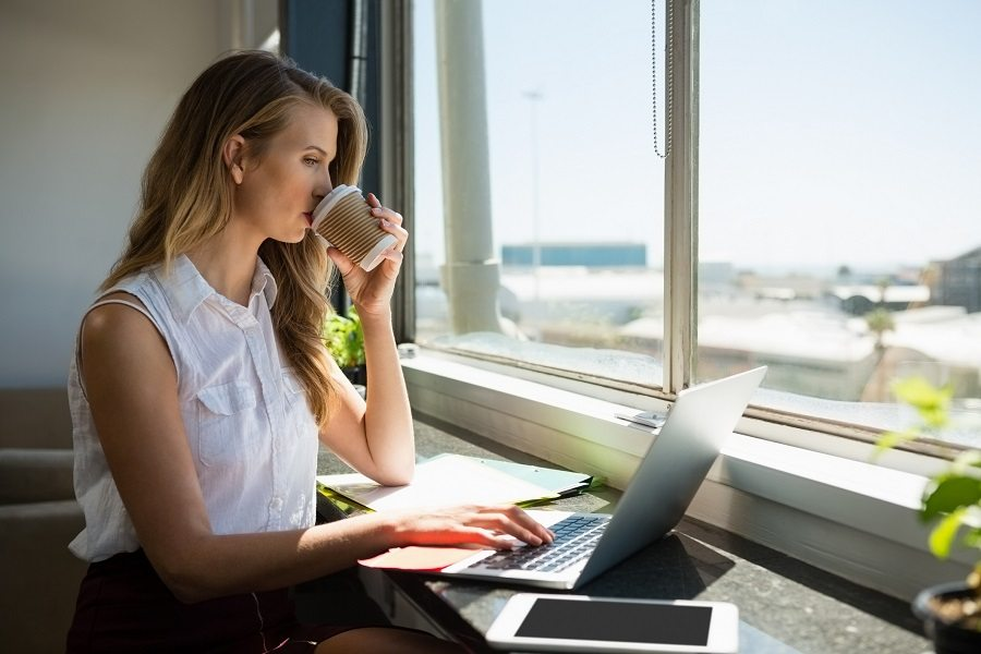 A woman using her laptop and drinking coffee