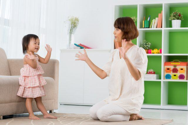 A mother and child clapping together.