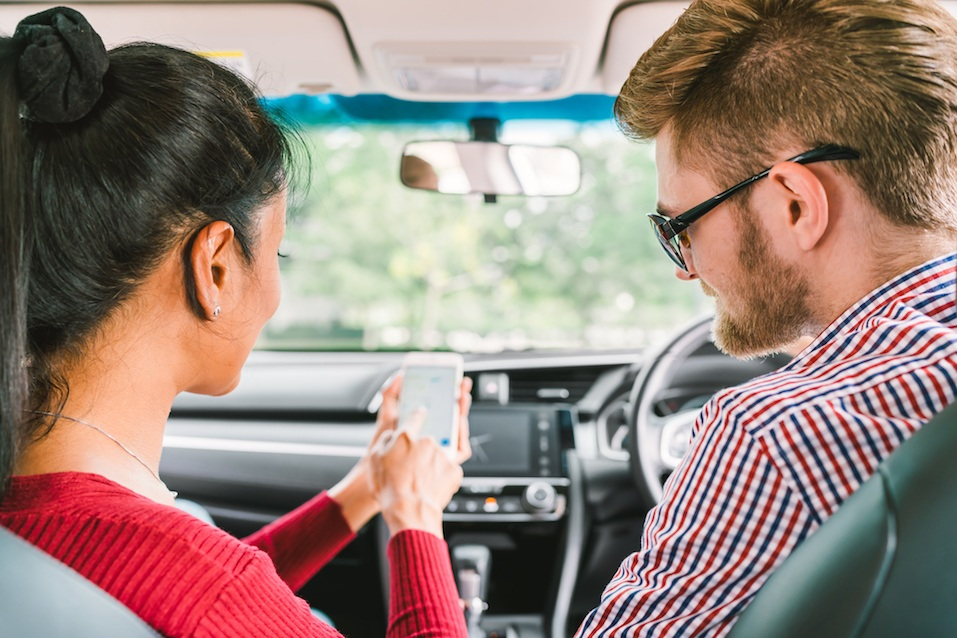 White man and black Asian girl using navigator system app on smart phone in car