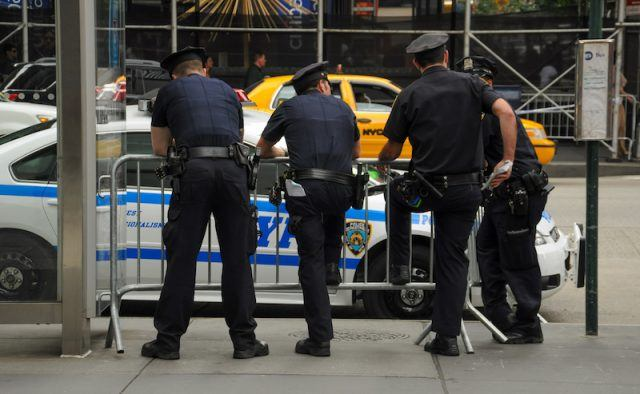 NYPD officers leaning on a metal barrier.