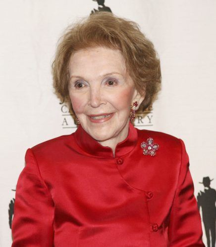 Nancy Reagan smiling in a red suit.