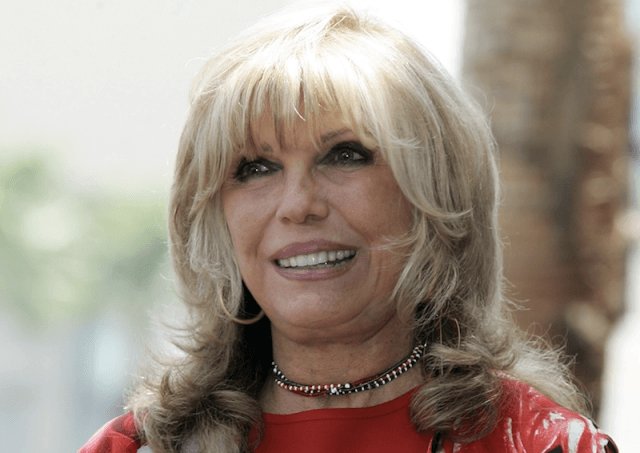 Nancy Sinatra smiling while wearing a red dress.