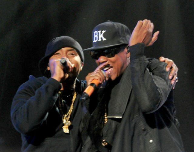 Rappers Nas and Jay-Z performing on stage.