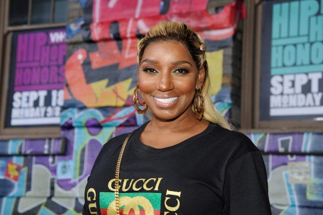 NeNe Leakes smiling while standing in front of a colorful background of posters and street art.