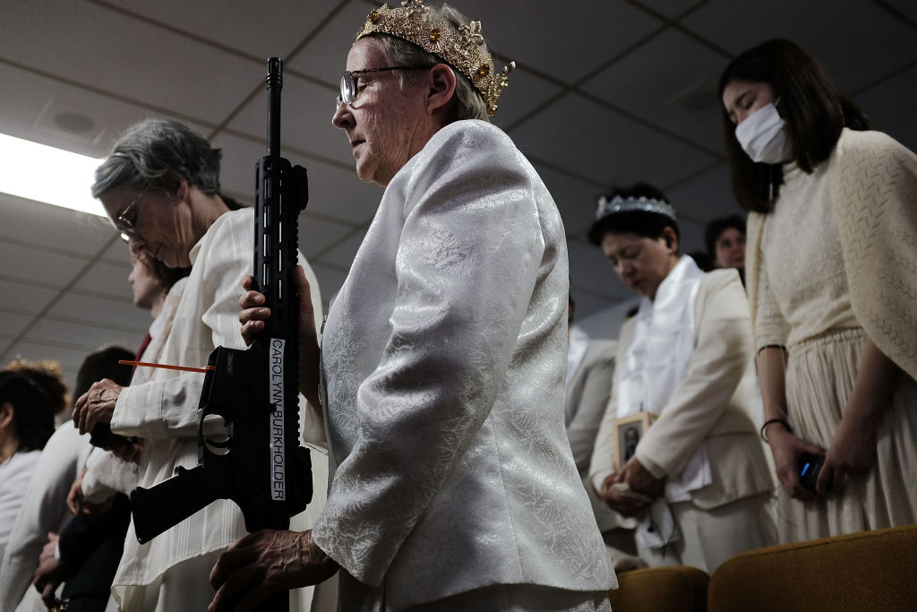 A woman holds an AR-15 rifle during a ceremony at the World Peace and Unification Sanctuary in Newfoundland,
