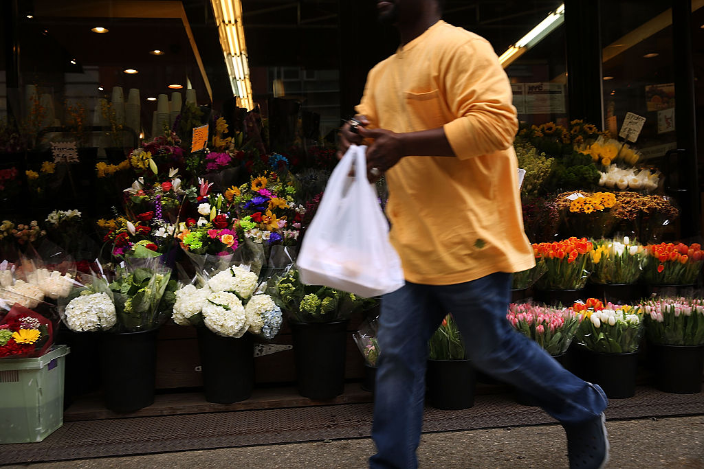 A man walks out of a supermarket with a plastic bag