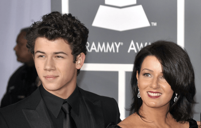 Nick Jonas standing with his mother on a red carpet.
