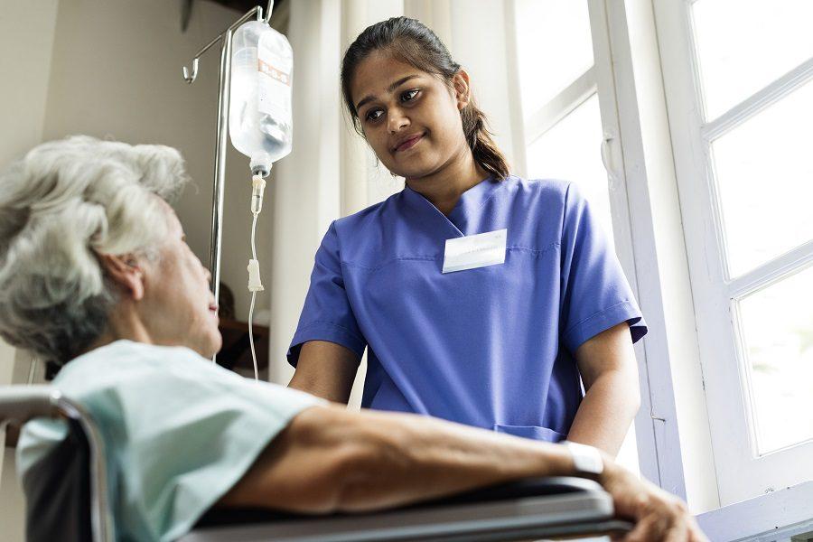 Nurse standing with elderly patient