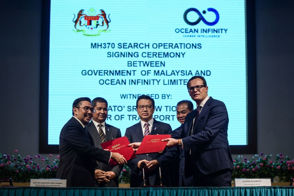 Director general of Malaysia's Civil Aviation Department (DCA) Azharuddin Abdul Rahman (L) exchanges documents with CEO of Ocean Infinity Limited Oliver Plunkett
