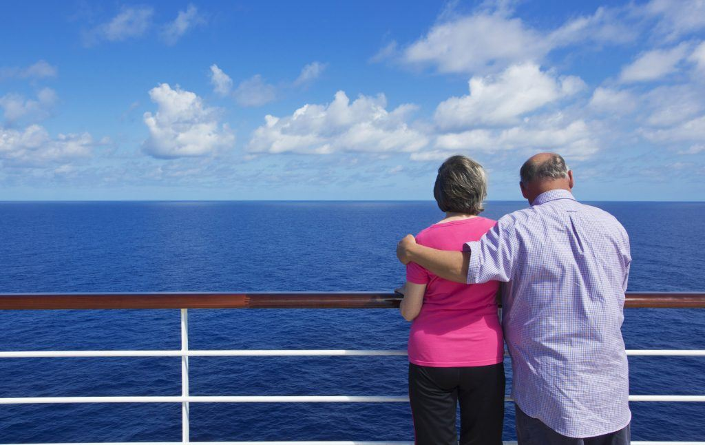 A senior couple looking out at the ocean on a cruise