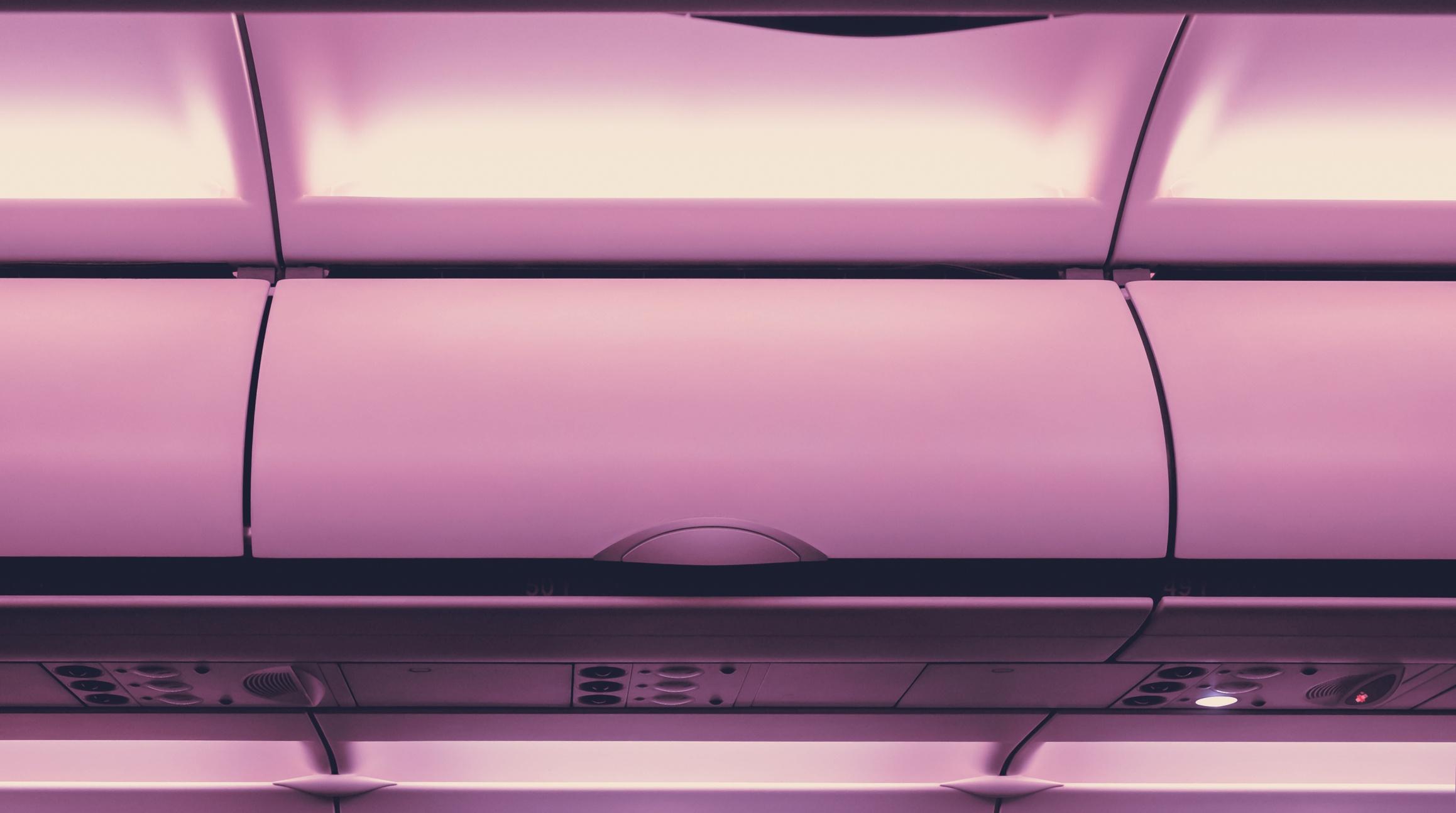 Close overhead bin of airplane with purple cast
