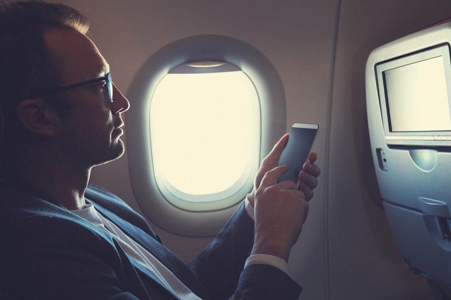 Man using smartphone in the airplane.