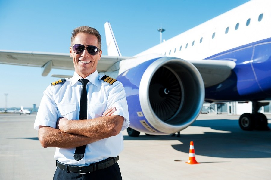 Confident male pilot in uniform keeping arms crossed and smiling with airplane in the background