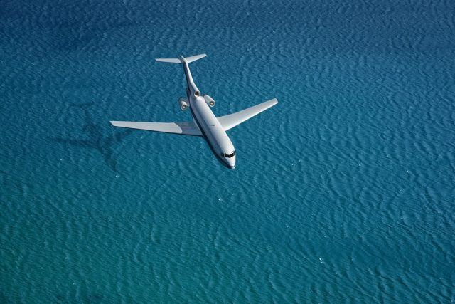 Airplane flies over a sea.