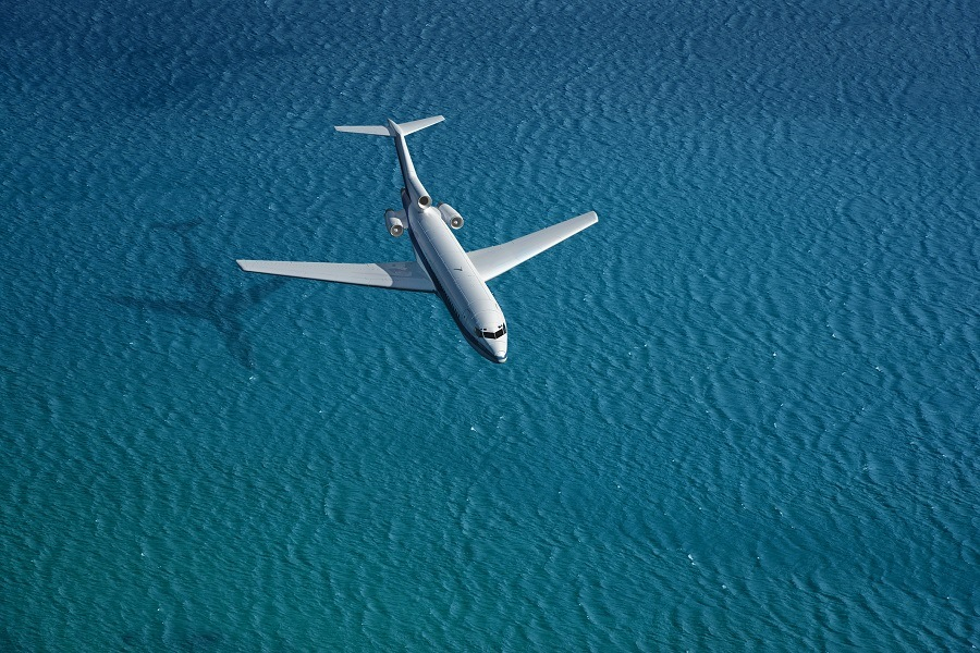 airplane flies over a sea