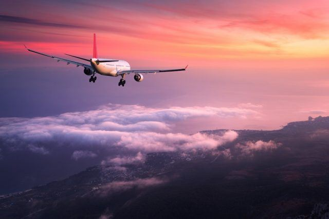Airplane is flying in the red sky.