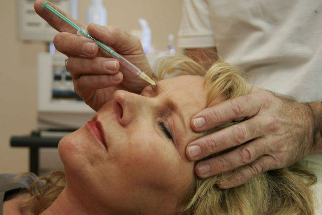 A doctor injects a patient with Botox at a cosmetic treatment center