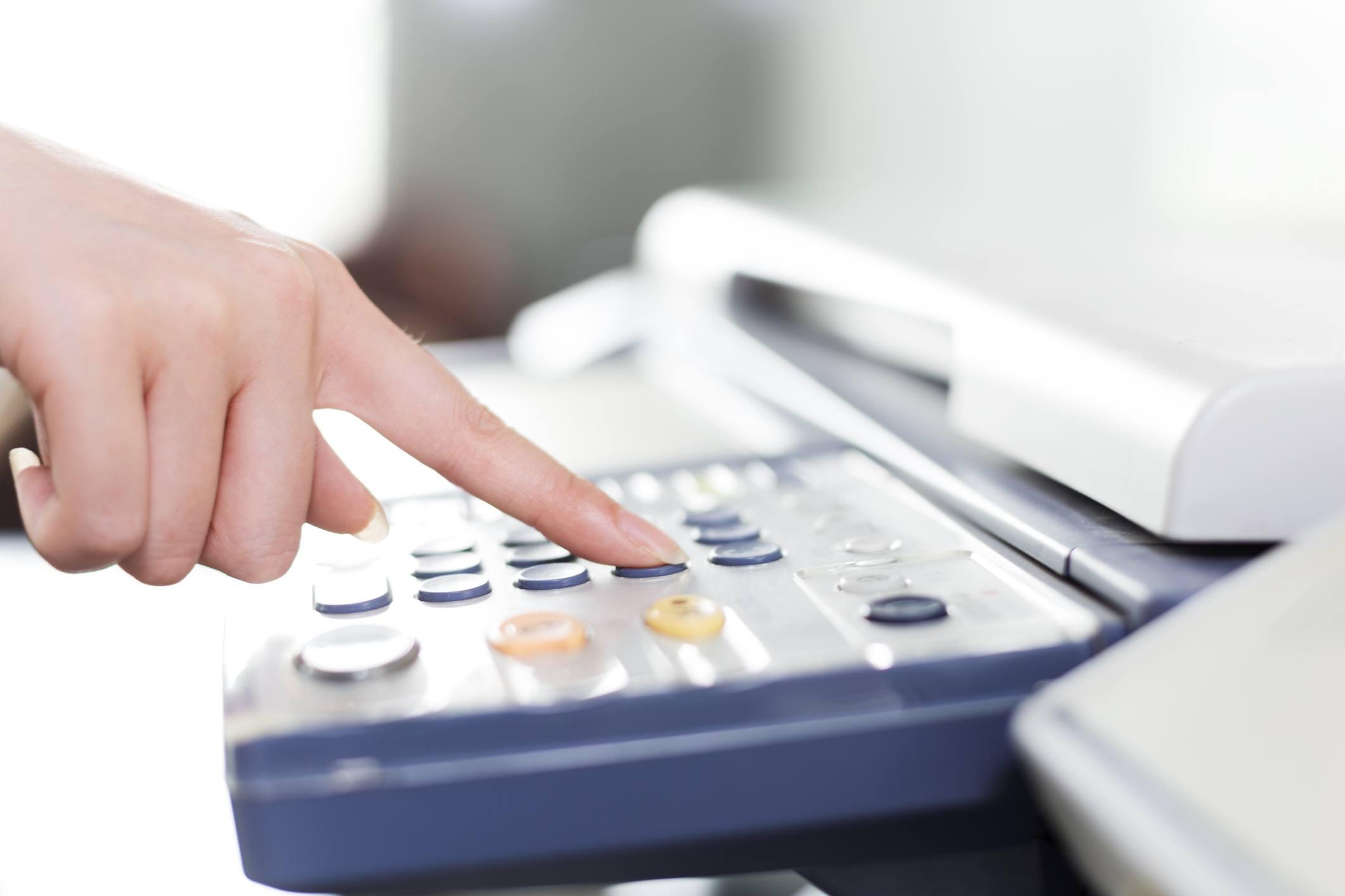 girl's finger presses button of copier