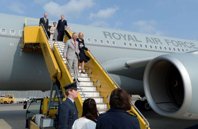 Prince Charles and Camila walking down the stairs of a jet.
