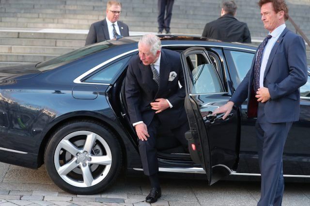 Prince Charles emerging from a black car.