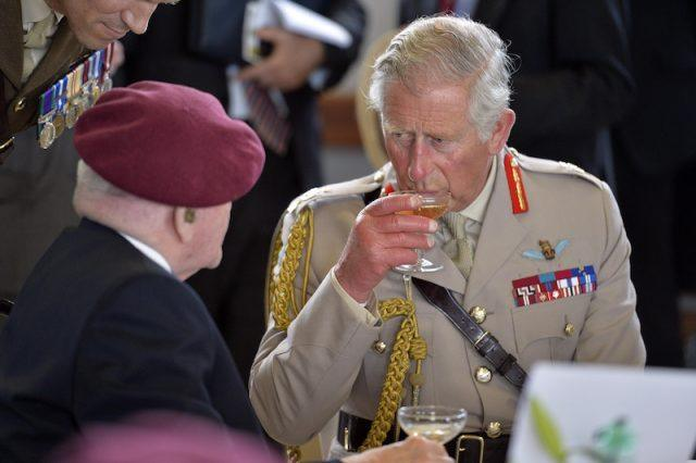 Prince Charles enjoying martini while socializing at an event.