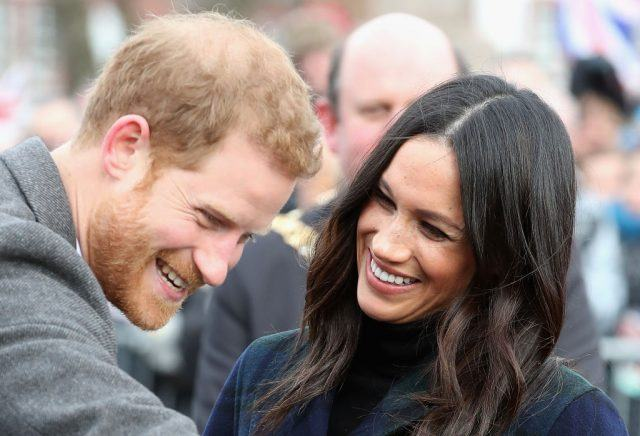 Prince Harry laughs and looks downward as Meghan Markle looks at him.