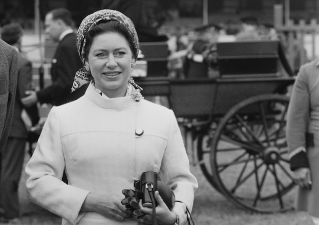 Princess Margaret holding a camera and gloves.