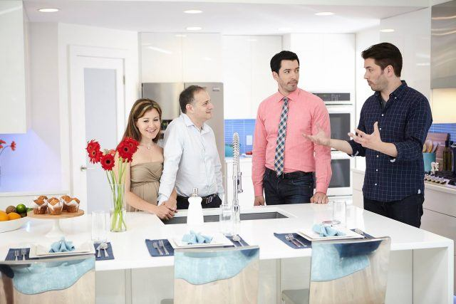 The Property Brothers chatting with a couple.