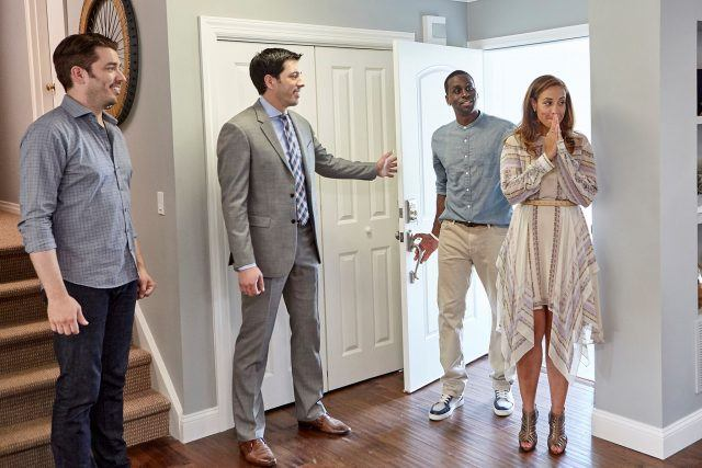 The Property Brothers revealing a home to a couple.