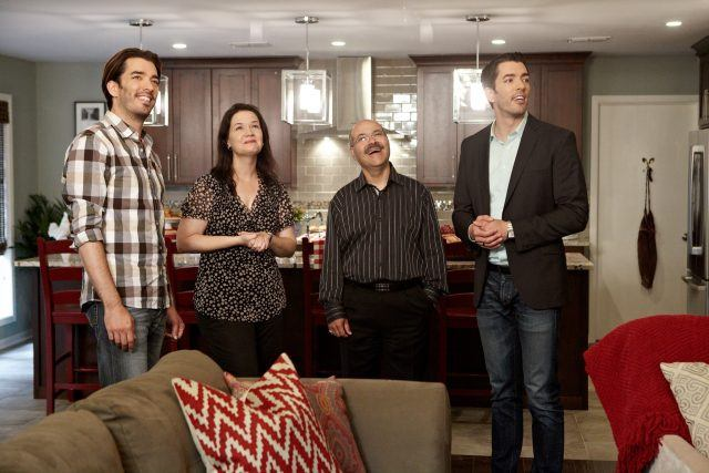 The Property Brothers showing a home to a couple.