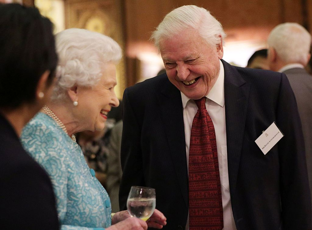 Britain's Queen Elizabeth II (L) reacts as she talks with television presenter David Attenborough