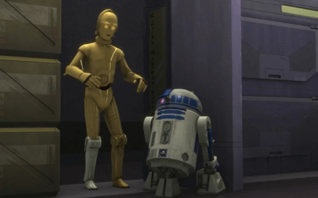 R2-D2 AND C-3PO standing together in a hallway.