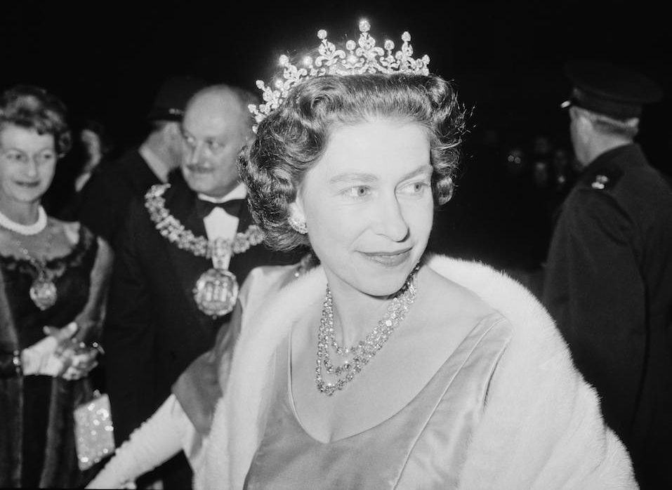 A black and white photo of a young Queen Elizabeth II attending a performance.