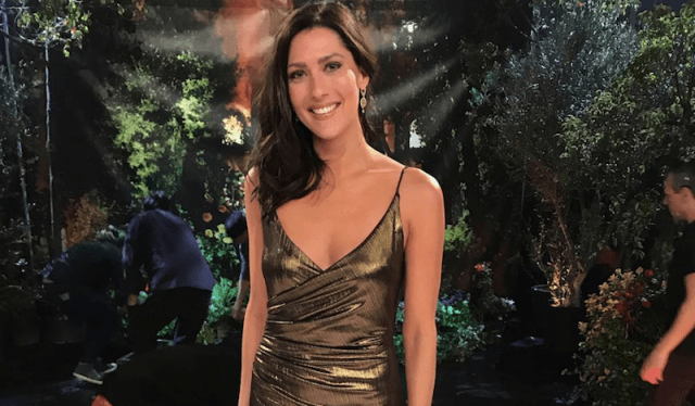 Rebecca Kufrin smiling while wearing a gold metallic gown.