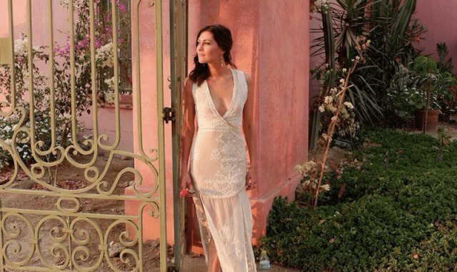 Rebecca stands in a white dress against a pink building?