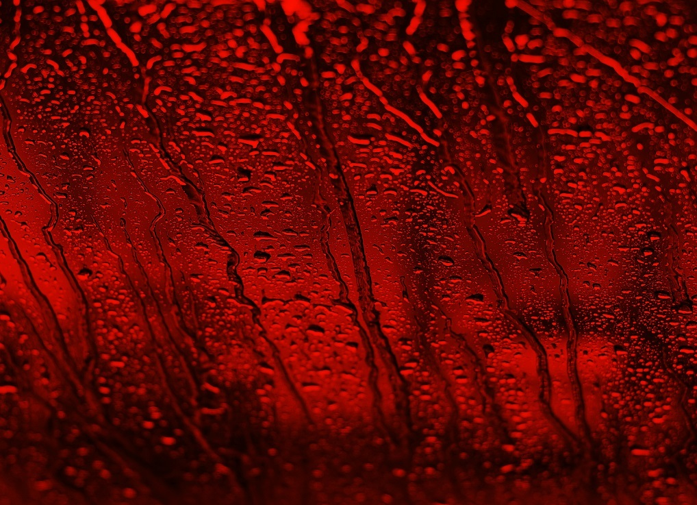 Dark red toned drops of water on the glass.