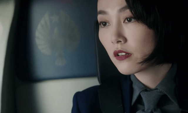 Mako Mori looks focused while wearing a dark suit.