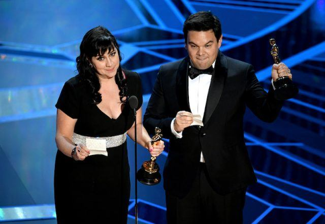 Kristen Anderson-Lopez and Robert Lopez accepting their awards on stage.