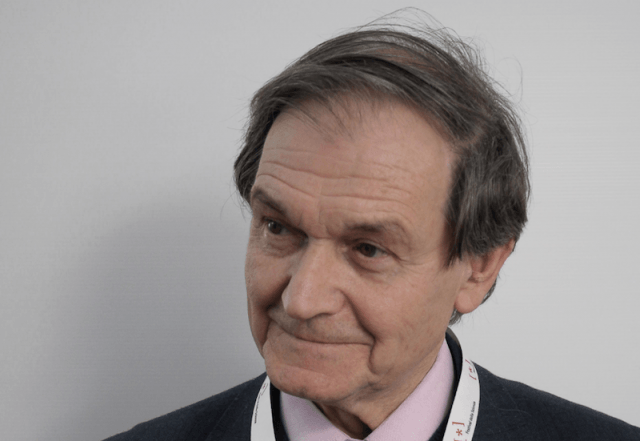 Roger Penrose standing in front of a white wall.
