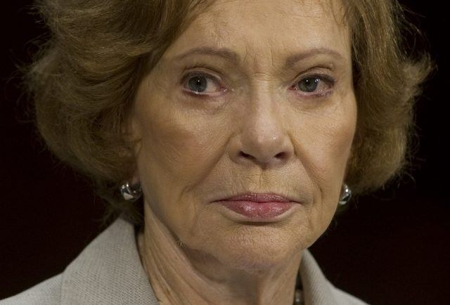 Rosalynn Carter standing in front of a black background.