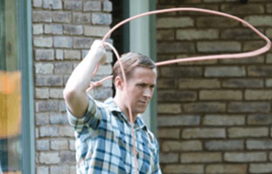 Ryan Gosling swinging a rope in 'First Man'.