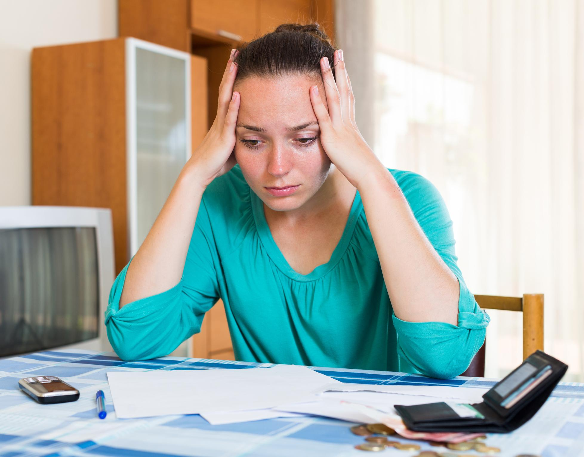 stress woman sits with her bills on the table
