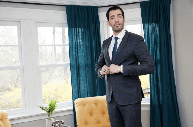 Drew Scott standing in a suit while inside a home.