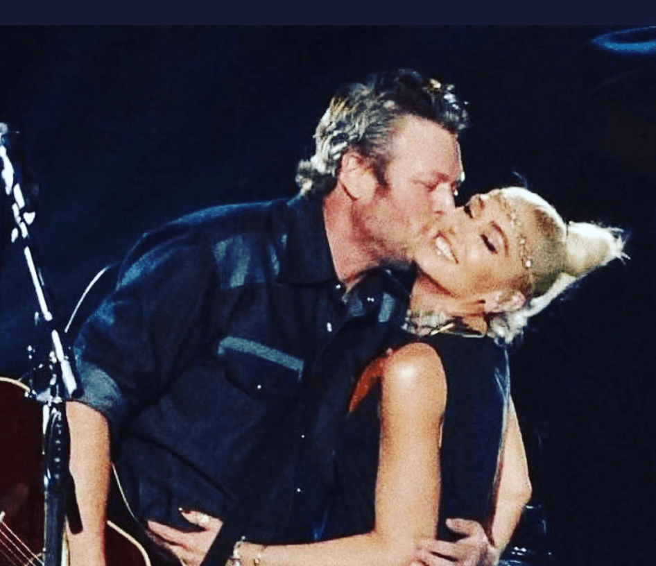 Gwen Stefani and Blake shelton smile on stage