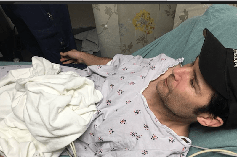 Corey Feldman in a hospital bed
